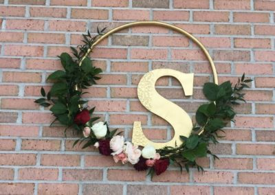 Hanging wreaths are a huge trend right now as a personalize, unexpected accent decoration that doubles as a great backdrop for pictures. Different options include large hoop over cake or guest book table, the hanging garden over head table, full floral wreath on the front doors or Custom hanging floral installations/displays.